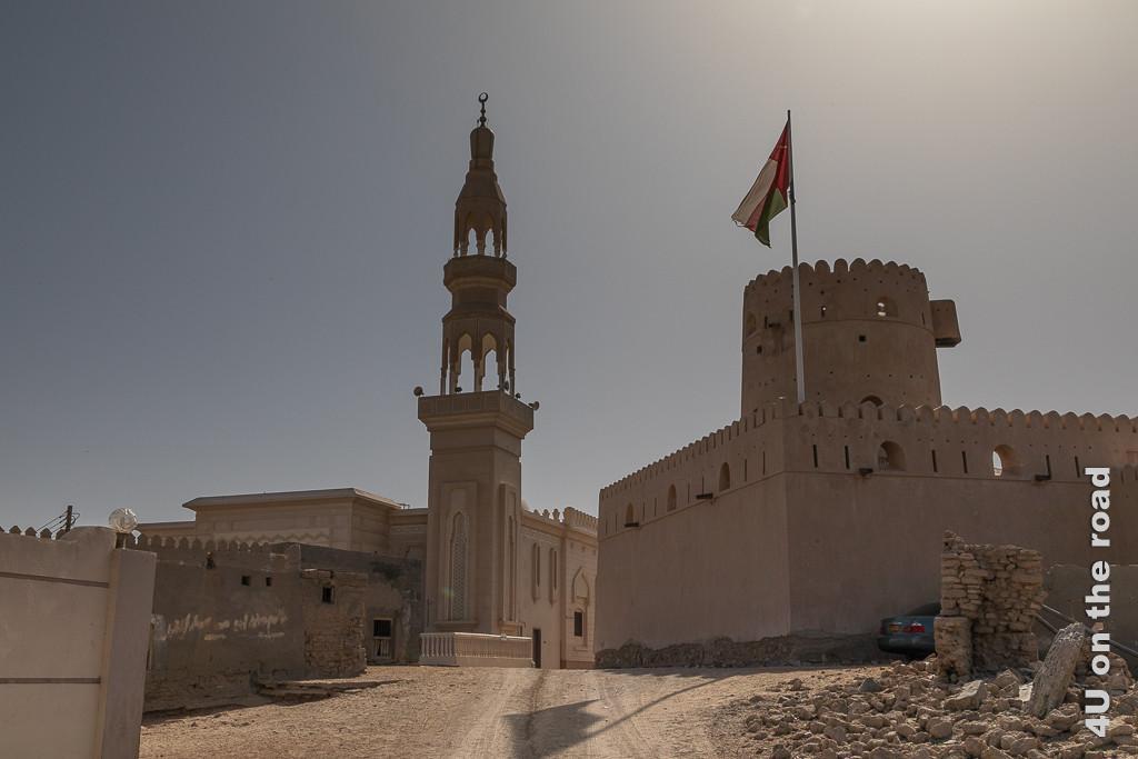 Bild Ras al Hadd - Moschee und Castle zeigt die von einem unbefestigten Weg von der Burg getrennte Moschee. Vom burgähnlichen Schloss ist hier nur einer der Wehrtürme zu sehen.