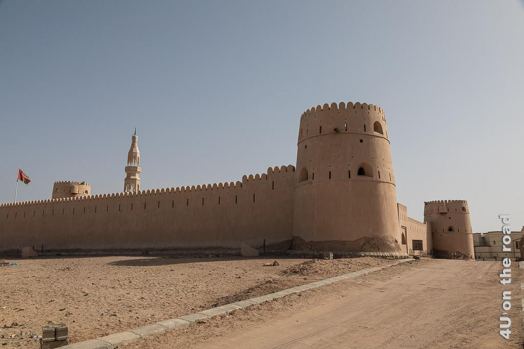 Bild Ras al Hadd - restauriertes Schloss zeigt zwei Fluchten der festungsähnlichen Anlage. Drei Wehrtürme und der Turm der Moschee sind im Bild zu sehen. An brökelnden Stellen kann man sehen, dass die Anlage mit Steinen gemauert wurde und nur einen Lehmputz erhalten hat.