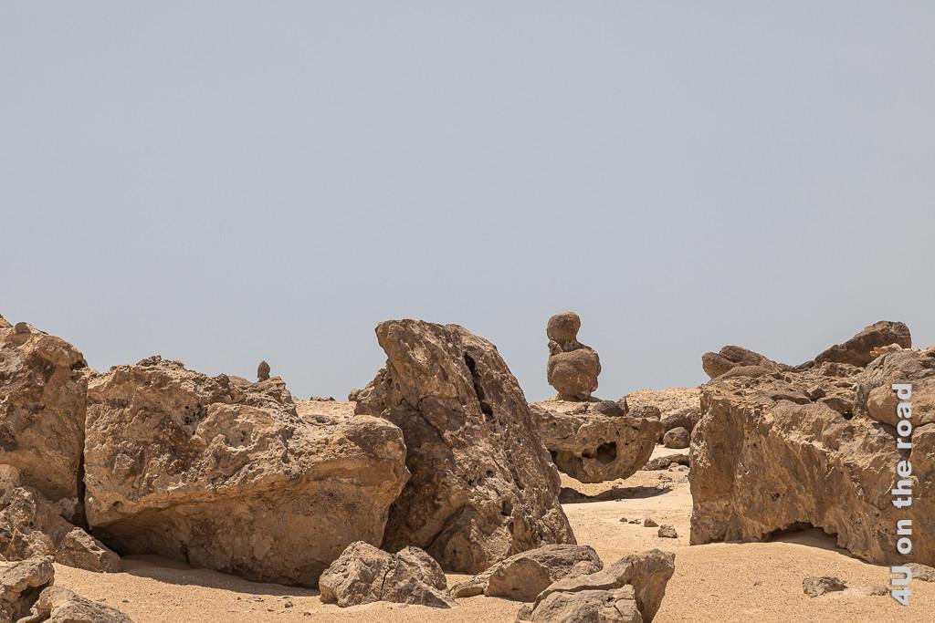 Rock Garden, Duqm - Seher in der Wüste zeigt einen auf einem Stein hockenden Gnom in Denkerpose.