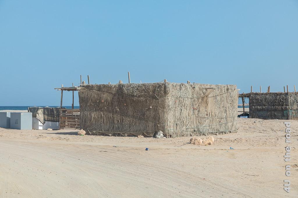 Ras al Hadd - Hütten zum Trocknen von Sardinen. Bild zeigt Palmwedel gedeckte Hütten. Die Palmwedel werden zusätzlich von Fischernetzen mit Gewichten befestigt.