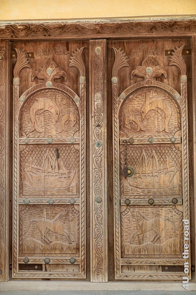 Ras al Hadd - schöne alte Holztür. Die zweiflügelige Holztür hat geschnitzte Motive: unten galopierendes Pferd, in der Mitte ein Dhau mit Segeln, oben zwei springende Delfine.