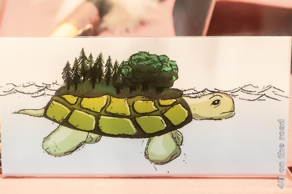 Bildnerische Darstellung der Schildkröte, welche die Erde trägt, zeigt eine Schilkröte auf deren Panzer sich oben die Erde mit Bäumen befindet.