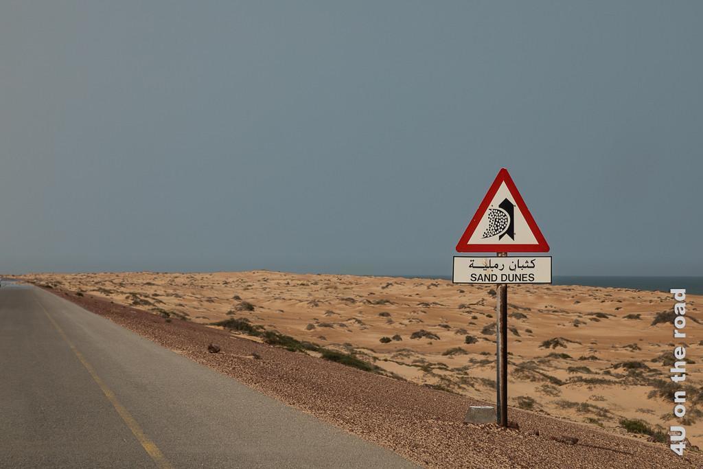 Warnschild Achtung Dünen Bild zeigt rotes Dreieck, in der Mitte ein schwarzer Pfeil, der halb durch eine Sandwolke von links kommend, verdeckt wird