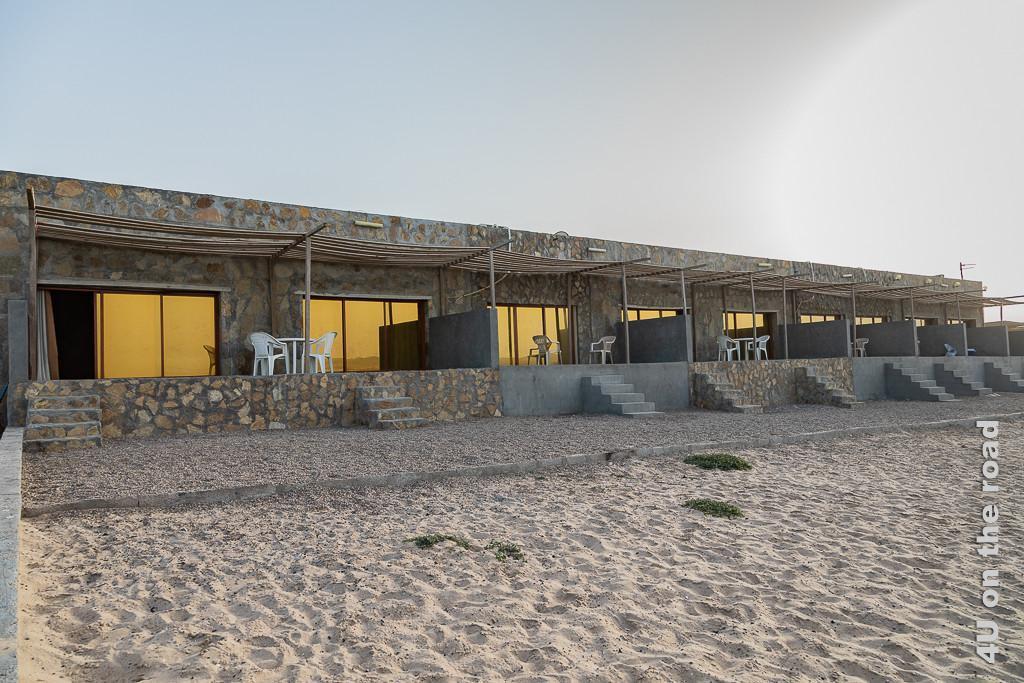 Saqla Resort - Bungalows am Strand zeigt die aus Natursteinen gemauerte, aneinandergebaute Bungalow Reihe mit Treppenabgängen zum Meer. Die Terrassenfenster sind gelb verspiegelt.