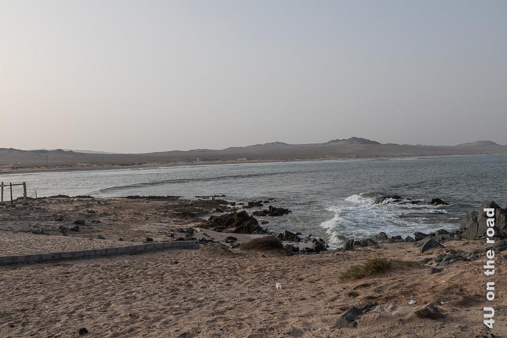 Saqla Resort - Blick von der Terrasse auf die Bucht und eine der Grillstellen. Bild zeigt die Meeresbucht mit den sich leicht erhebenden Felsen. Die Wellen laufen schräg in die Bucht rein.