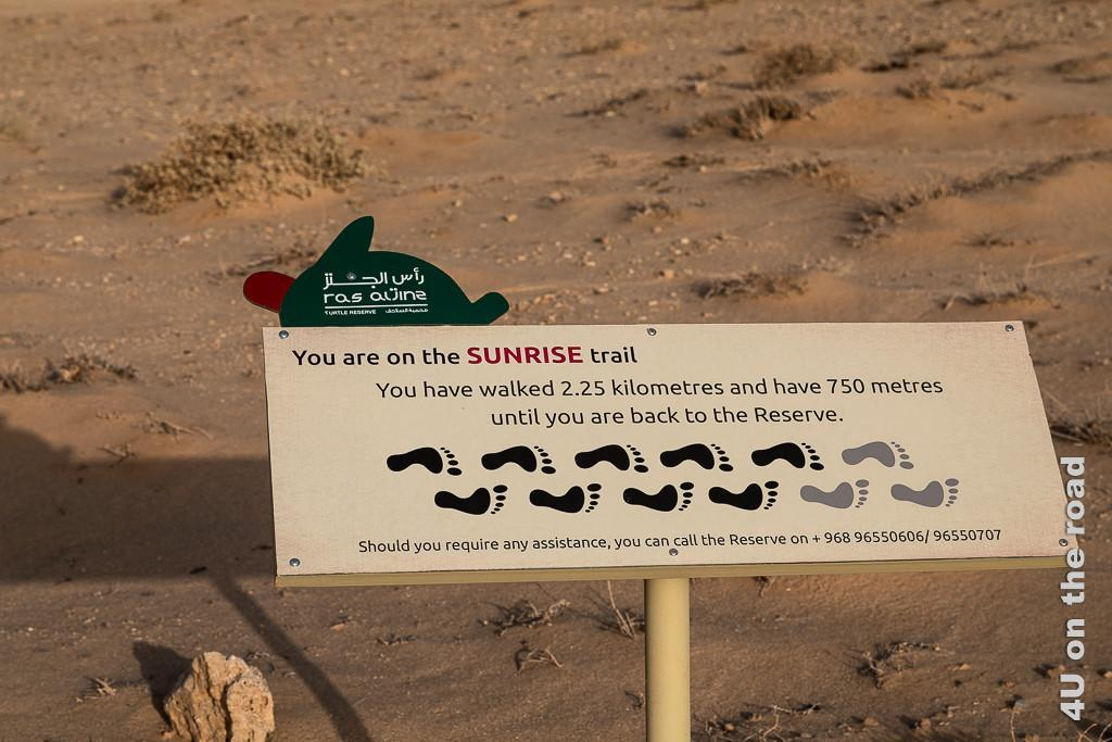 Ras al Jinz - Motivationsschild. Bild gibt Auskunft, dass man sich auf dem Sunrise Trail befindet und bereits 2,25 km geschafft hat und es noch 750 m bis zum Hotel sind. Über eine Telefon-Numer kann man Hilfe holen.