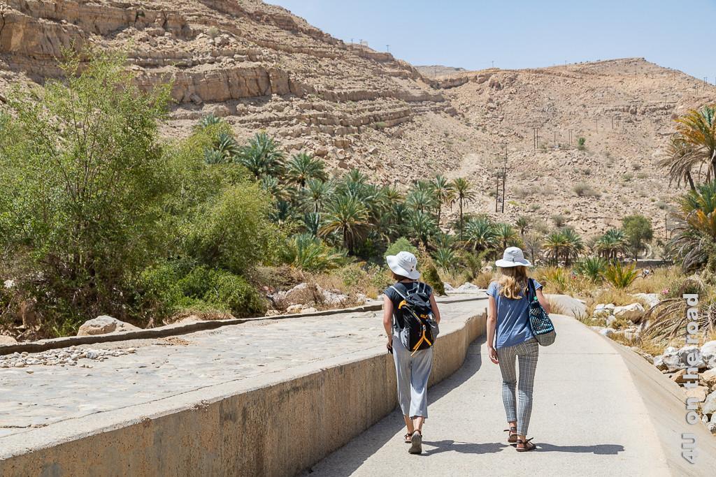 Wadi Bani Khalid - Auf dem Weg zu den Rockpools zeigt unsere Töchter auf dem neu betonierten Weg neben dem Falaj Kanal ins Tals, welches von Bergen umgeben ist.