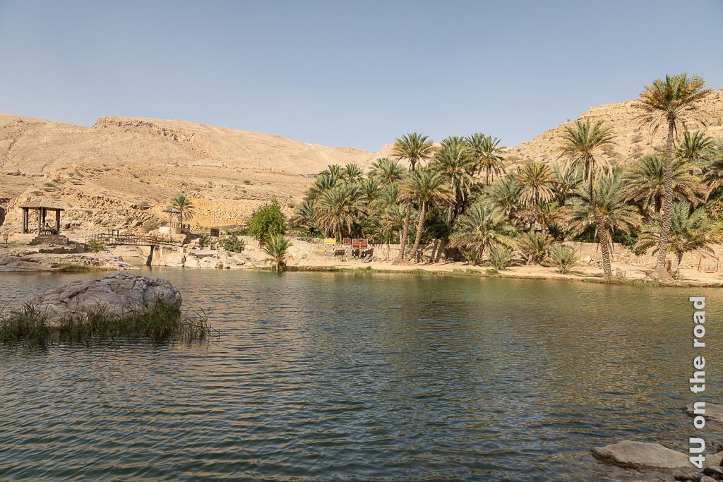 Wadi Bani Khalid - Blick auf die Brücke. Hinter der Brücke fängt der Talabschnitt mit den Rockpools an. Rechts säumen Palmen den Uferrand neben dem Wasser. Links hinten sieht man die Brücke, die an einem Pavillon vorbei führt. Im Hintergrund erheben sich die Berge.