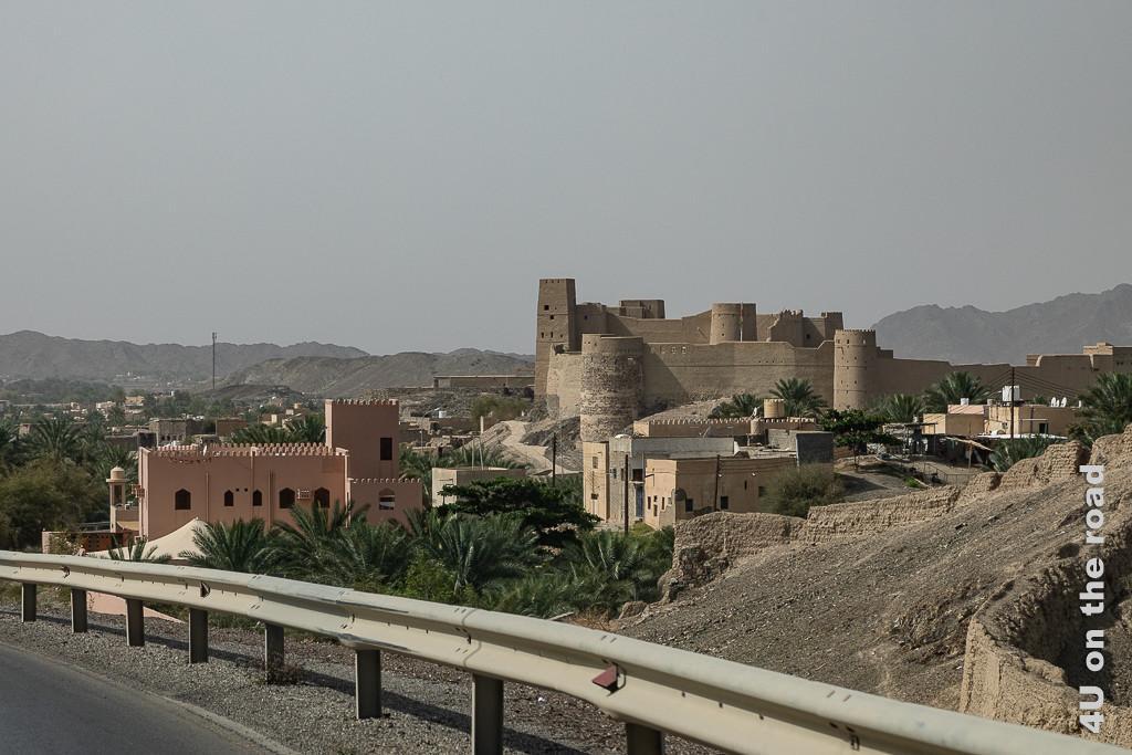 Bahla Fort und Reste der alten Stadtmauer zeigt das mächtige Fort auf dem Hügel von der Strasse aus und die neben der Strasse verlaufende alte Stadtmauer.