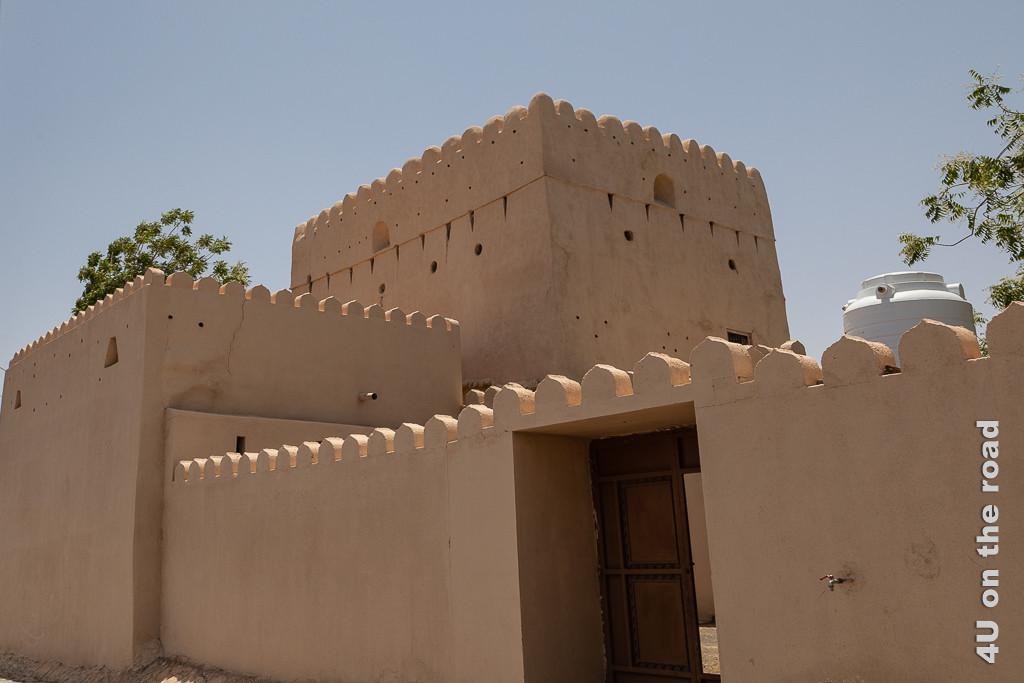 Al Mudayrib - Wohnfestung. Dieses Haus in Lehmputzoptik bestehend aus zwei rechteckigen Türmen umgeben von einer hohen Mauer ohne sichtbare Fenster wirkt wie eine Trutzburg.