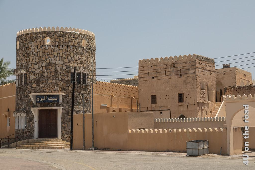 Al Mudayrib - Wohnfestungsanlage - Ein Turm mit Fenstern erhebt sich links. An ihn schliessen hohe Mauern an. Daneben befinden sich Wohntürme in U-Form hinter doppelten Mauern. Alles ist mit Zinnen geschmückt.