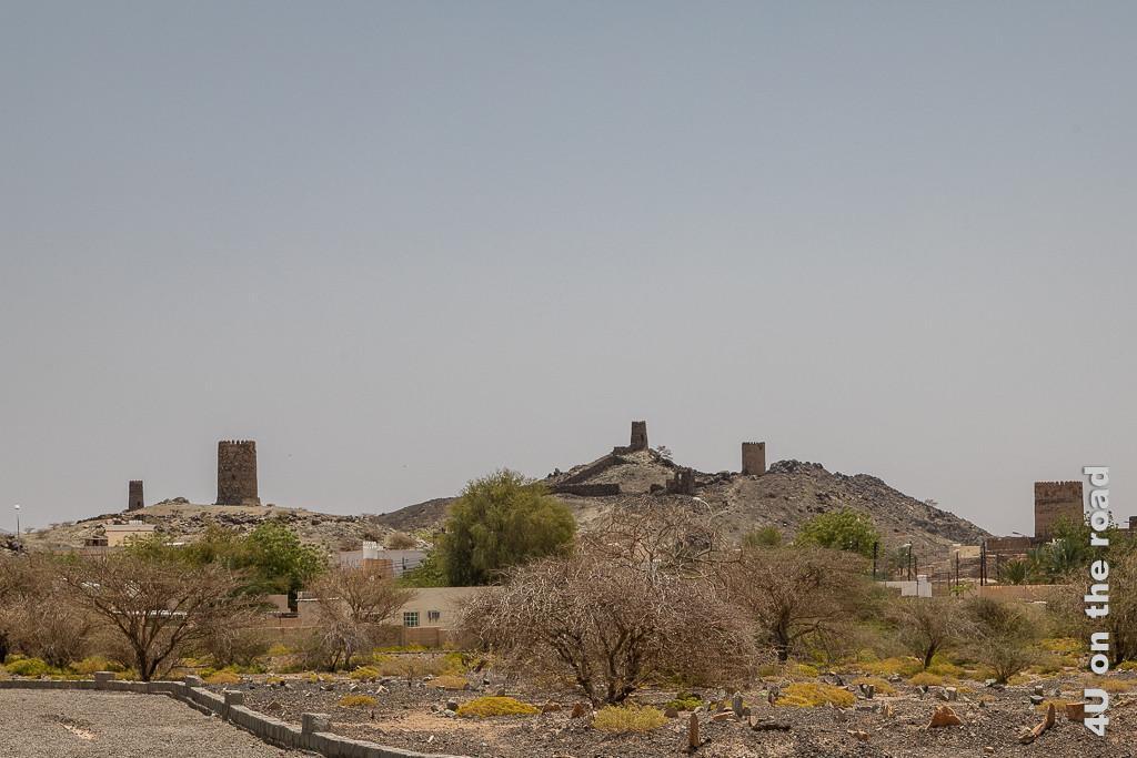 Wachtürme von Al Mudayrib. Das Bild zeigt fünf Wachtürme, vier stehen auf Hügeln. Im Vordergrund wechseln sich trockene und grüne Bäume ab.