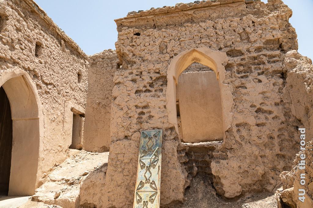 Al Mudayrib - Zwischen den Ruinen der Vergangenheit zeigt Häuser der Wände und Tür- und Fensterbogen noch stehen. Im Vordergrund lehnt ein Flügel einer Metalltür.