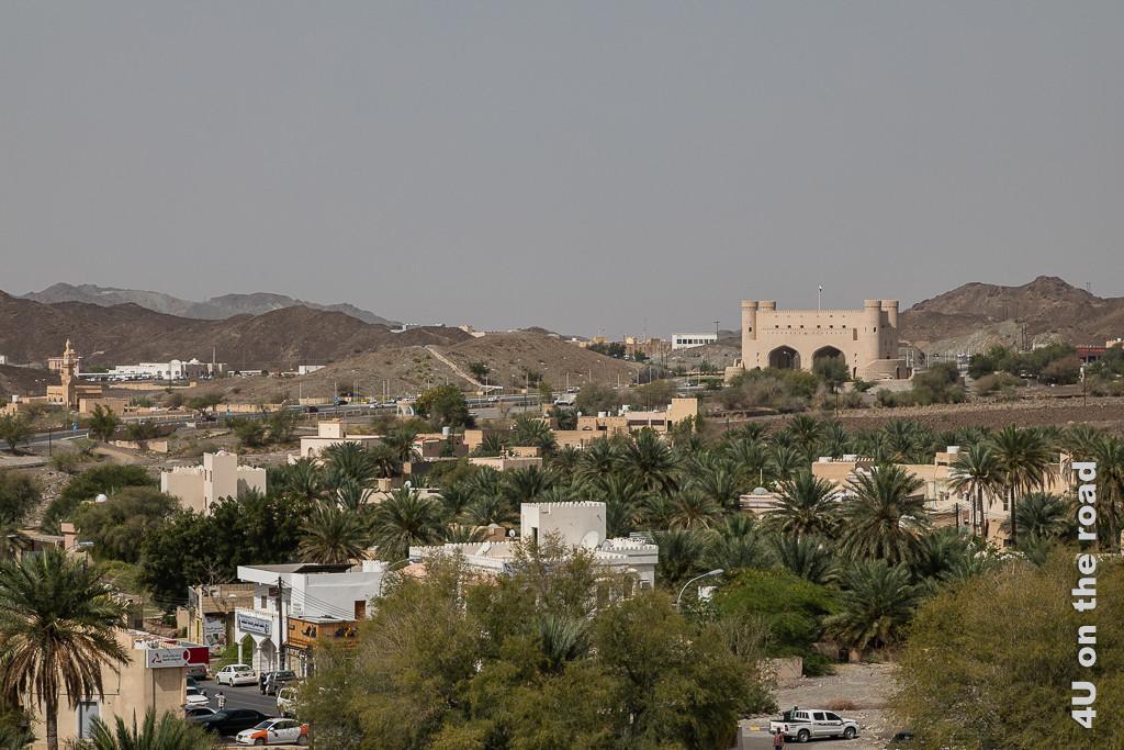Bahla - Blick von oben auf das moderne Stadtportal. Die Strasse wird durch grosse Tore geführt. Über den Toren erhebt sich eine Festung mit vier Wachtürmen. Bei genauem Hinsehen, erkennt man Teile der alten Stadtmauer.