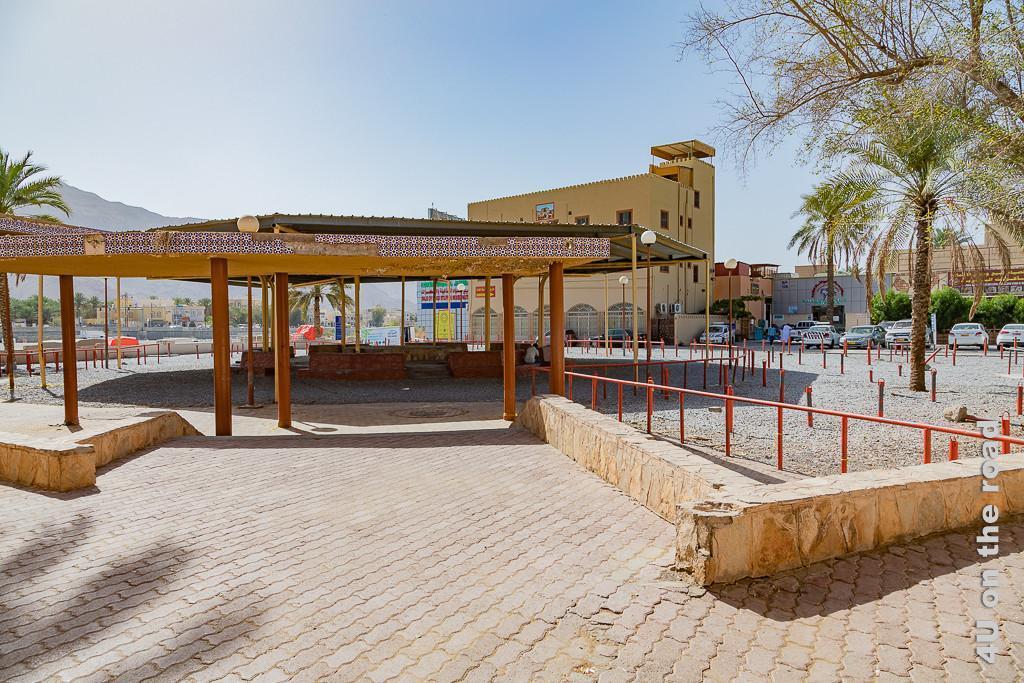 Nizwa Viehmarkt - Ein Dach auf Säulen über einem Kiesplatz mit im Kreis angeordneten Bänken im Schatten. Drumherum orange Geländer und Pfosten mit Bügeln zum Befestigen von Vieh