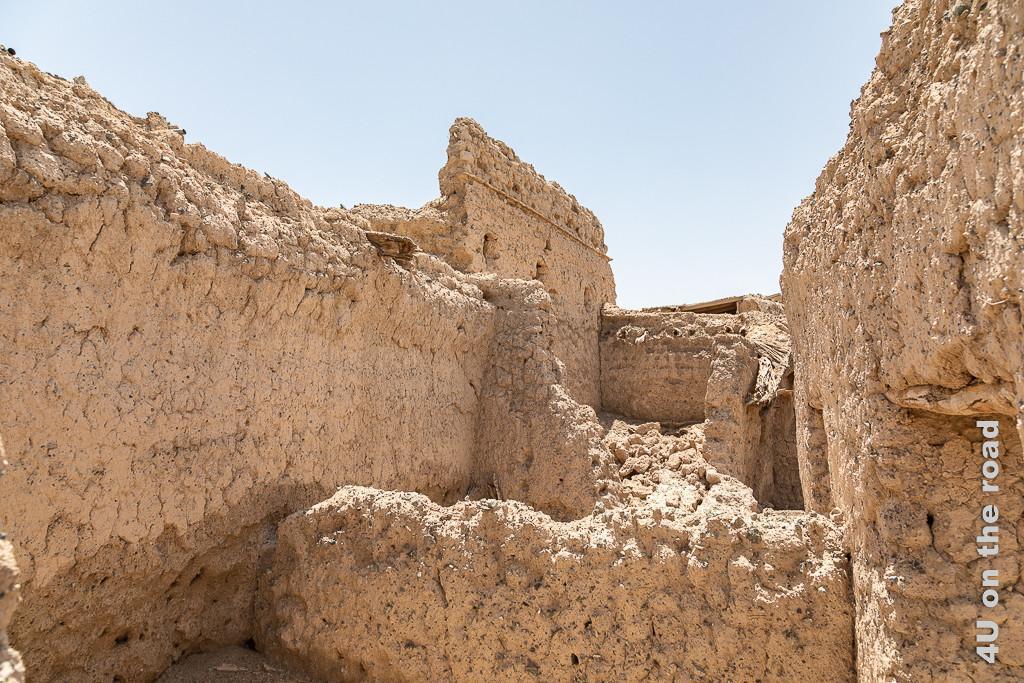 Al Mudayrib - Ruinen. Sie zerlaufen wie Sandburgen. Wände sind eingestürzt und die Steine ergiessen sich nach unten. Im Lehm und Kies des Verputzes erkennt man Steine, Fenster- und Türöffnungen ohne Sturz.