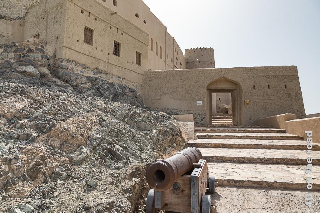 Eingang zum Bahla Fort. Auf nacktem Fels erhebt sich links die hohe Mauer. Rechts führt eine breite, flache Treppe zum unteren Toreingang an der äusseren Mauer. Ein kleine Kanone zeigt auf das Fort.