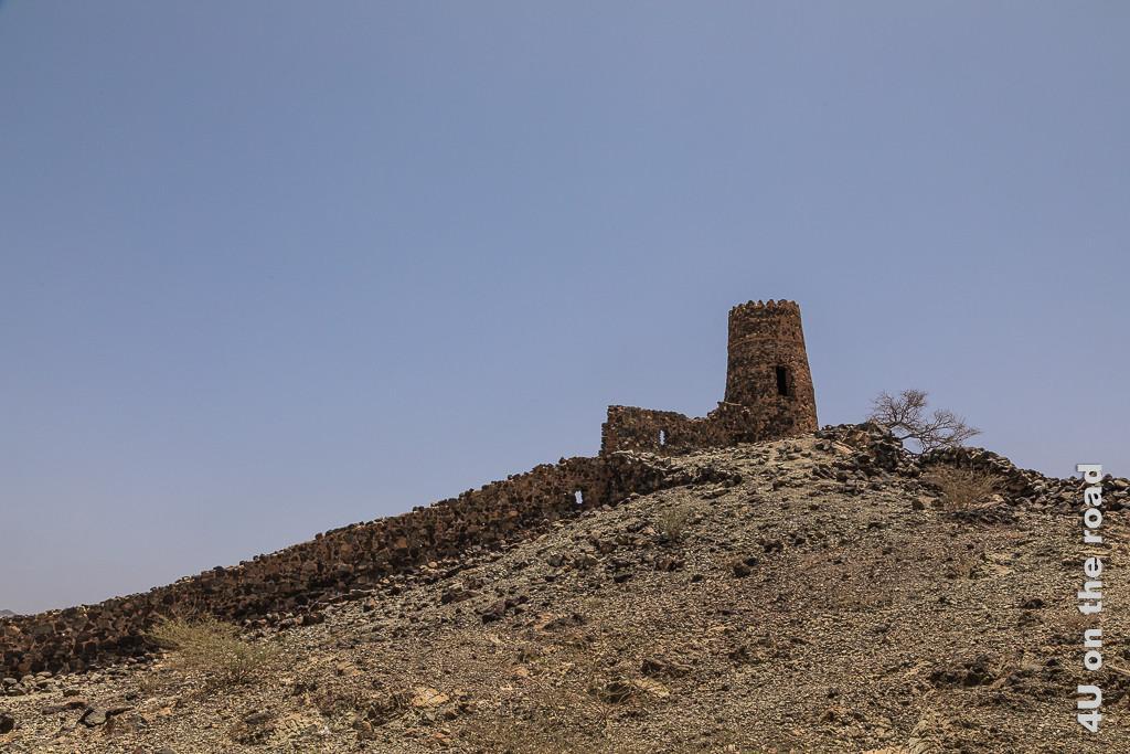 Al Mudayrib - Wachturm auf dem Berg mit Mauer. In Turmnähe hat die Mauer Fensteröffnungen.