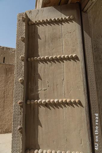 Bala Fort - Der gewaltige Torflügel ist geöffnet. Das hohe doppelflügelige geöffnete Tor besteht aus einfachem, dicken Holz mit kunstvollen Schnitzerein an den Balken und dicken Holzdornen.