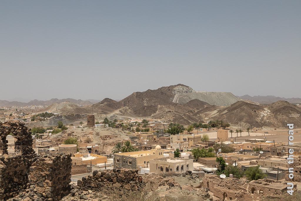 Al Mudayrib - Blick von oben auf die Ausläufer des Hajar Gebirge und Wohnfestungen. Ein weiterer Wachturm und Reste der dicken Staudtmauer sind zu sehen. Moderne und verfalle Wohnfestungen stehen in direkter Nachbarschaft.
