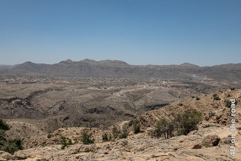 Auf 2015 m Höhe Blick auf Al Sheraija beim Jebel Al Akhdar. Im Bild sieht man ein grosses Felsplateau hinter dem sich eine massive Felswand erhebt. Auf dem Plateau erkennt man den Ort.