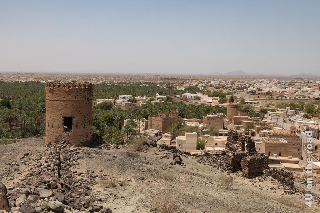 Al Mudayrib - Blick vom unteren Wachturm auf dem Hügel auf den städtischen Wachturm und die sich darum gruppierenden Wohnfestungen. Der Palmengürtel endet auf der Hälfte des Bildes.