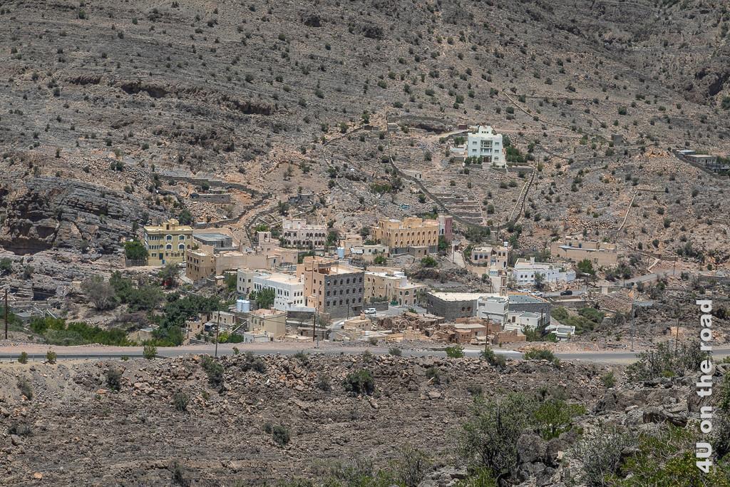 Dorf in einem Seitental der Strasse zum Jebel Al Akhdar. In diesem kleinen Dorf stehen grosse 3-geschossige Häuser entlang des Berghangs. alte Lehmhäuser verfallen.