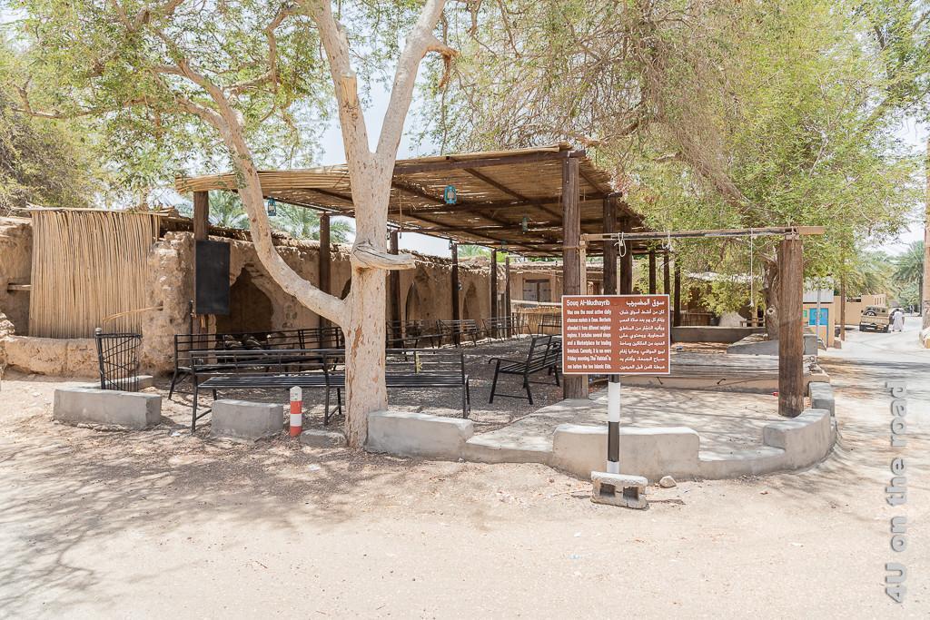 Souq von Al Mudayrib. Der Souk ist von Bäumen umgeben. Unter einem Schattendach stehen rundherum Bänke. Verkaufsläden befinden sich auf der einen Seite hinter Mauern.