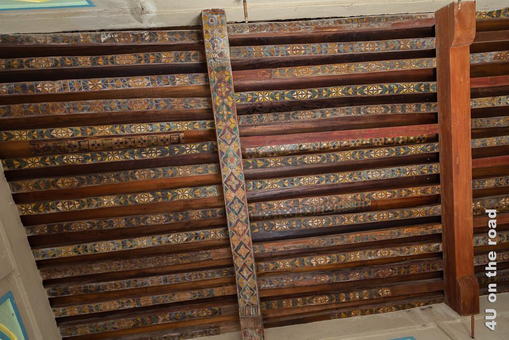 Bahla Fort - Kunstvoll bemalte Deckenbalken im Raum mit den hohen Regalnischen und den niedrigen Türen. Auf den Deckenbalken sind farbige Ornamente gemalt.