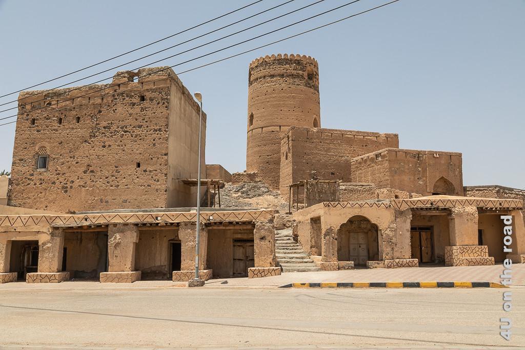 Al Mudayrib - Der städtische Wachturm - Bait Al Burj. Im Bild ist die ganze Anlage von der Strasse aus gesehen, abgebildet. Ein Säulengang wird in der Mitte durch eine Treppe, welche zum Gebäude unterhalb des Turms führt, unterbrochen. Im Schatten des Säulengangs erkennt man geschlossene Türen. Links erhebt sich ein weiteres grosses, fast fensterloses, quadratisches Gebäude