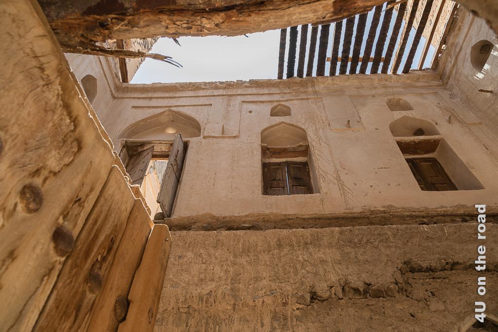 Im Inneren einer alten Wohnfestung. Das Bild zeigt die intakten Seitenwände des Hauses mit Fensteröffnungen und Fensterladen. Das Dach fehlt. Nur noch einige Holzbretter liegen darüber. Genauso fehlt der Zwischenboden zwischen den beiden Etagen. Man sieht aber, wo er aufgelegen hat.