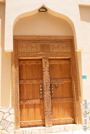 Al Mudayrib - Holztür. Die zweiflügelige Holztür hat wunderschöne Schnitzerein an den Seiten und dem Mittelpfosten. Querbalken und der Mittelpfosten sind mit Metalldornen versehen. Ein grosser Riegel mit Vorhängeschloss verschliesst die Tür