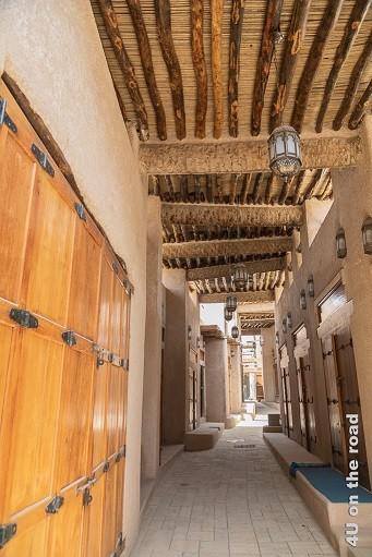 Bahla - Blick in den neuen Souk, auch wenn die Geschäfte geschlossen haben. Ein langer Gang mit einem Dach aus Rundholz und Schilf. Entlang des Ganges befinden sich die Läden hinter schönen verschlossenen Holztoren. Teilweise sind kleine Steinmäuerchen vorgemauert. Sie dienen dem Schutz vor Regenwasser und dem Sitzen.