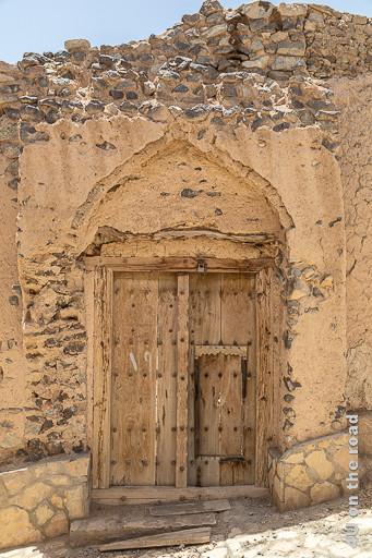 Al Mudayrib - Holztür in einem Eingangsportal einer Ruine. Die Tür ist zweiflüglig mit einem Balken in der Mitte. Auf der rechten Seite führt eine kleine Tür im Holzflügel nach Innen. Diese Tür hat keine Farbe mehr, die Metalldornen rosten oder fehlen. Im Mauerwerk sieht man noch die Vormauerung des Portals.