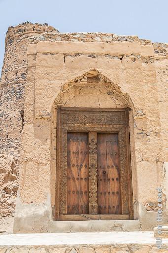 Al Mudayrib - dekorative Holztür. Diese Holztür schmückt ein nicht ganz intaktes Eingangsportal. Die Holzmaserung ist ist speziell. Die Balken an den Seiten, oben und in der Mitte sind kunstvoll geschnitzt. Metalldornen sind in 6 Reihen übereinander auf der Tür angebracht.