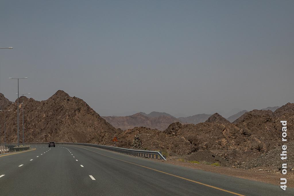 Durch das Hadjar Gebirge nach Nizwa. Im Bild sieht man die zwei Mal 3-spurige Strasse, welche durch das schroffe, spitze, dunkelbraune Gestein führt.