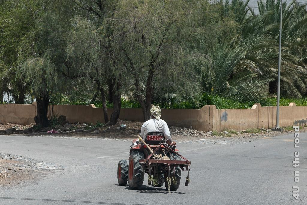 Kleiner Traktor für kleine Felder. Der Traktor hat einen kleinen Pflug mit drei Zinken angehängt und ist so schmal, dass eine Person gerade darauf sitzen kann. Der Bauer fährt vor uns auf der Strasse.