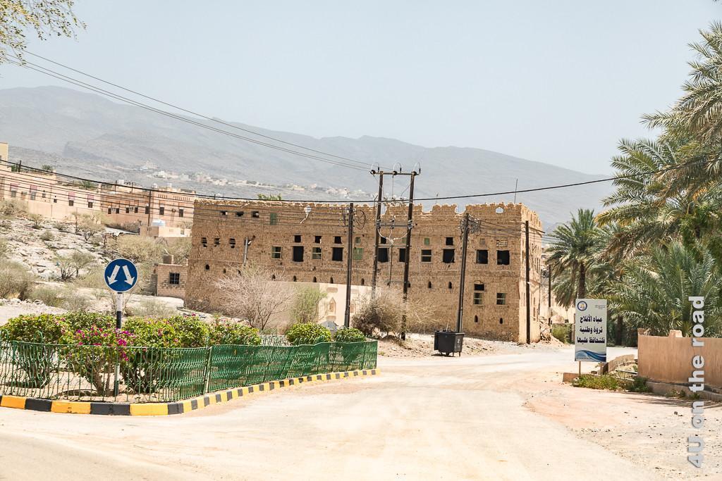 Al Hamra - Dieses Gebäude sieht schon einmal wie ein Lehmhaus aus. Hinter einer mit Rosen bepflanzten Strassenkreuzung erhebt sich eine grosses, mehretagige Lehmhausruine