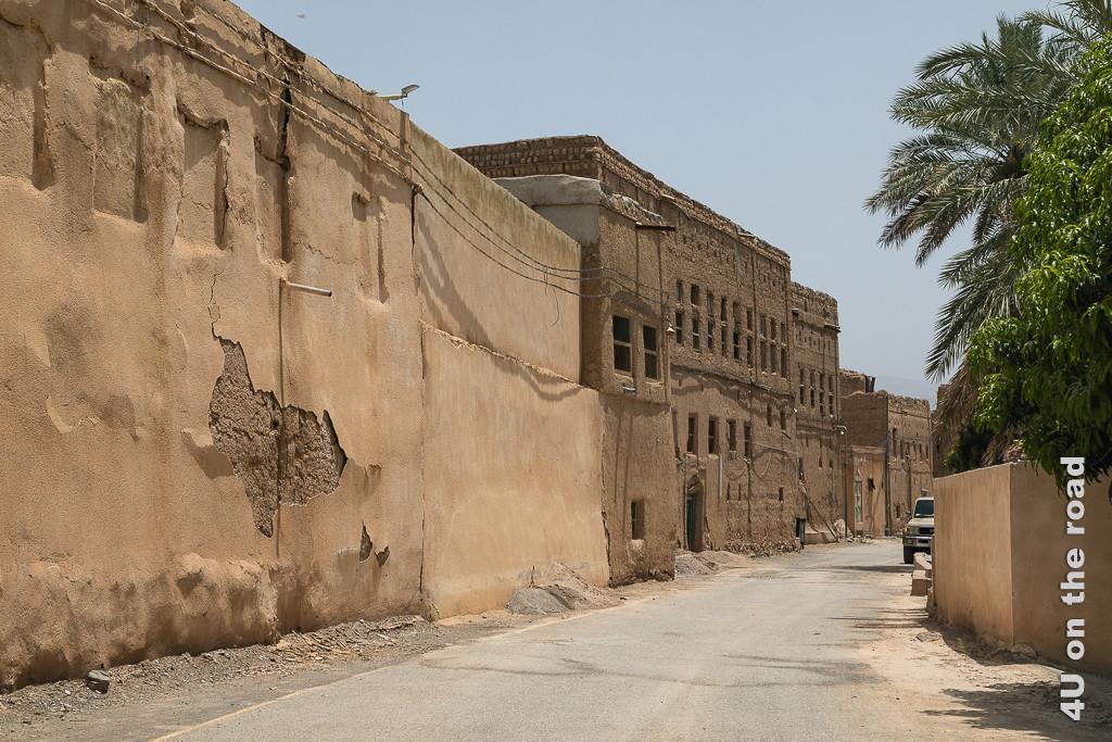 Al Hamra - hier müssen wir wenden, obwohl wir scheinbar richtig sind. Entlang der Strasse reiht sich ein grosses Lehmhaus ans andere. Auf der anderen Seite der Strasse befinden sich Palmengärten hinter Mauern