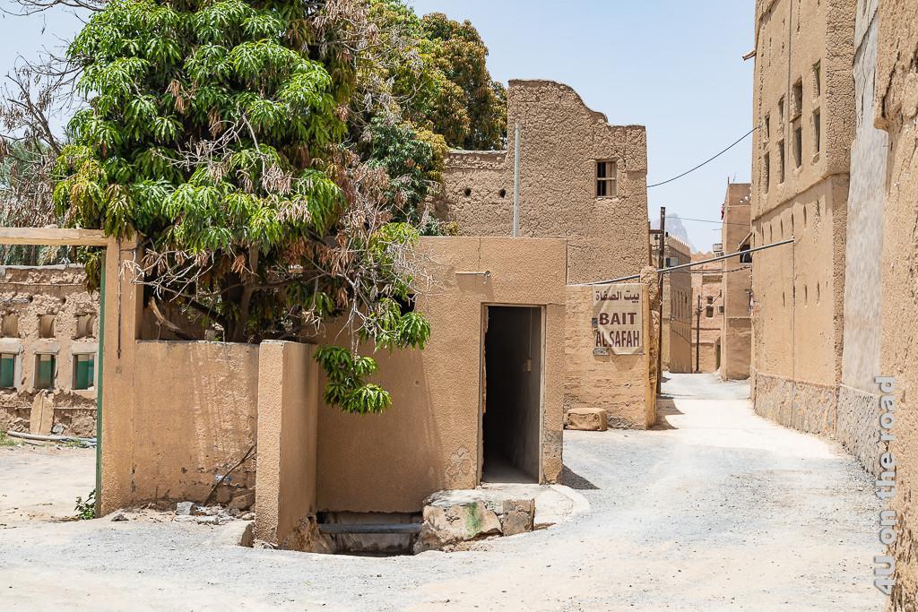 Al Hamra - Irgendwo hier muss der Eingang zum Museum sein. Im Bild sieht man links ein Torbogen und weitere Ruinen. Ein Baum ernährt sich vom Wasser des hier sichtbaren Falaj Wassergrabens. Auf einer Mauer hängt ein Schild mit dem Namen des Museums. Entlang des Weges steht ein Lehmhaus am anderen.