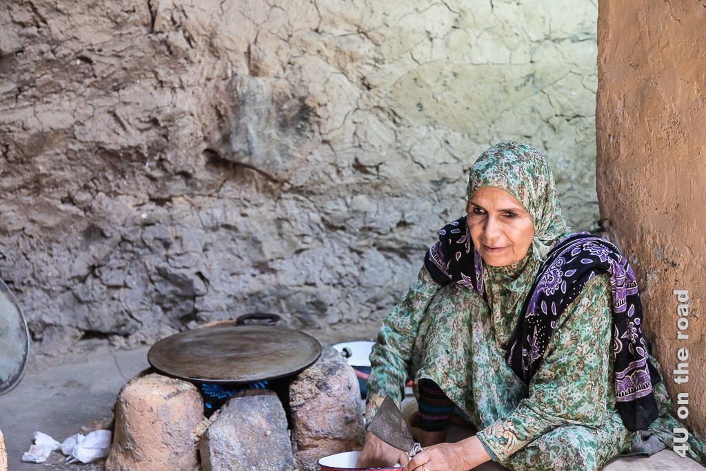 Im Museum Bait al Safah, Al Hamra - Auf dieser Eisenplatte wird das Brot gebacken. Im Bild sieht man eine ältere Frau auf einem Kissen auf dem Boden sitzend, mit den Händen in der Teigschüssel. Neben ihr bilden aufgeschichtete grosse Steine, um eine Gasflamme den Herd. Auf den Steinen liegt lose eine Metallplatte.