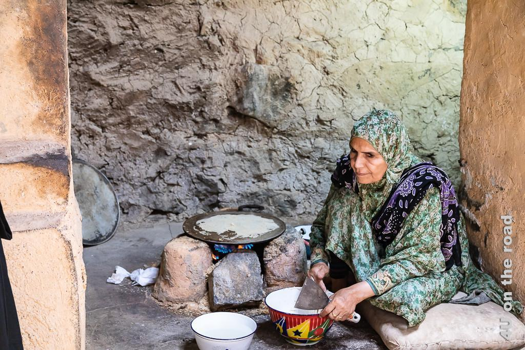 Im Museum Bait al Safah - Das auf die Platte getupfte Brot bäckt. Der Spachtel ist schon in der Hand der Frau, um das dünne Brot herunter zu kratzen.