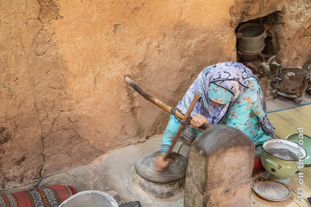 Im Museum Bait al Safah, Al Hamra - So wird das Mehl von Hand gemahlen. Auf dem Boden ist ein flacher Stein befestigt, auf dem ein runder Stein durch Hand angetrieben rotiert. Dazu steckt im oberen Stein ein langer Stocker, welcher mit eine Lederband an einem Querstock, der in der Hauswand und einem Pfosten befestigt ist. Die Frau fasst den Stock knapp oberhalb des Steins und bewegt damit den Stein.