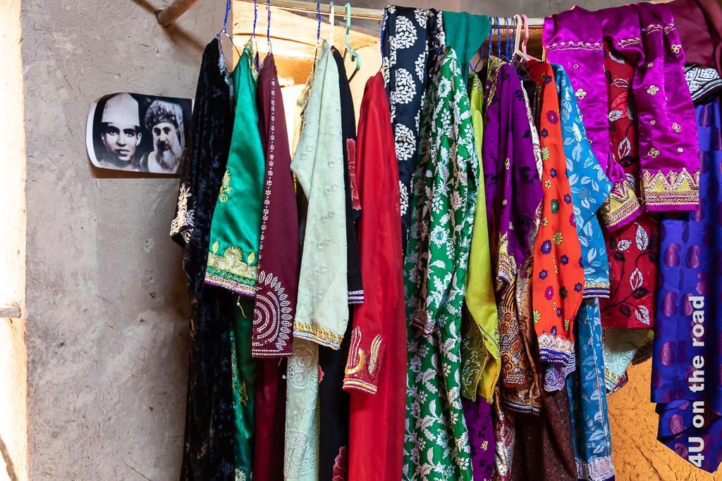 Im Museum Bait al Safah, Al Hamra - Die Kleider sind zum Teil aufwändig bestickt. Auf einer Kleiderstange hängen 14 Kleider und Hosen in den unterschiedlichsten Farben und Schnitten. Ein Foto vom Sultan als Kind und als alter Mann schückt den Raum.