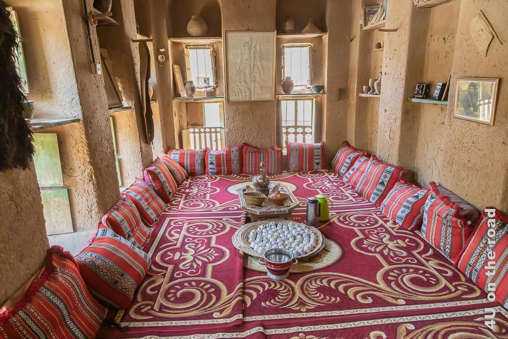 Das Wohnzimmer im Museum Bait al Safah, Al Hamra - Hier werden die Besucher zu Kaffee, Tee und Datteln eingeladen. Auf dem Boden liegen Teppiche, Kissen lehnen an der Wand. An zwei Seiten des Raums befinden sich Fenster.