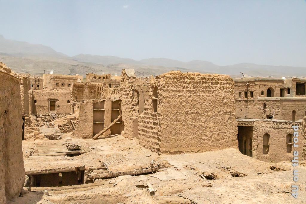 Al Hamra - Blick über die Dächer der Stadt. Man sieht jede Menge weiterer Ruinen von Lehmhäusern, die teilweise höher gebaut sind, als die Terrasse von der ich fotografiere. Auf einem Haus steht eine Satelitenschüssel.
