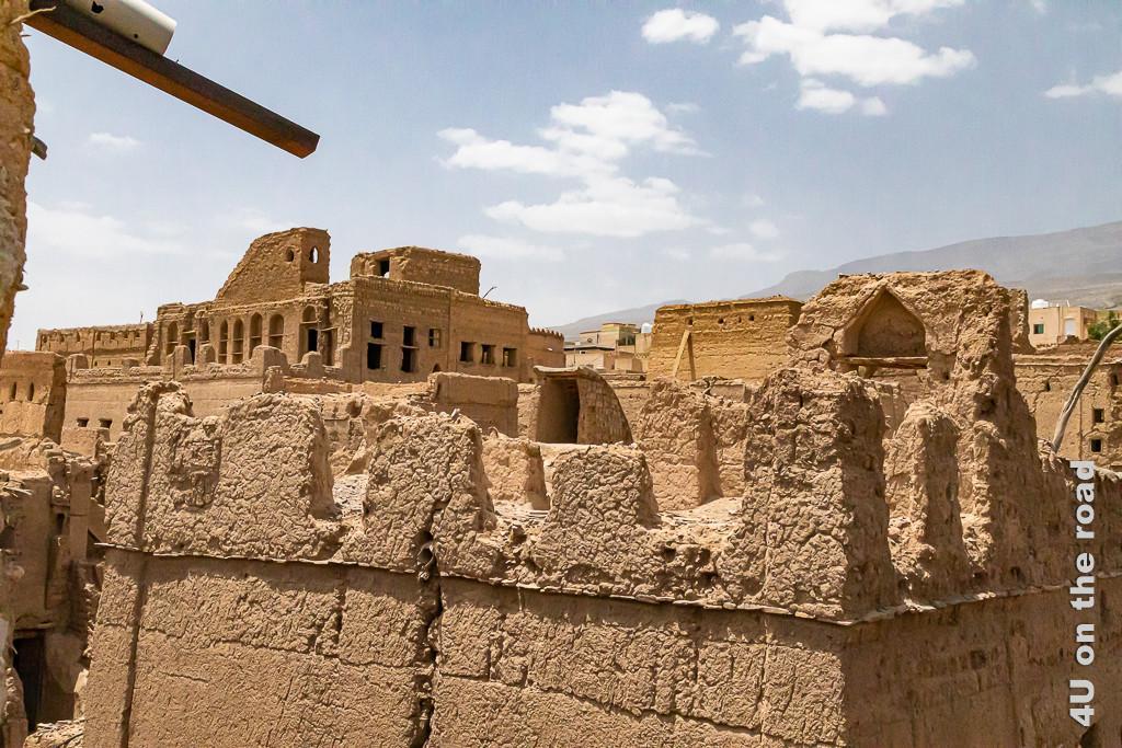 Al Hamra - Blick über die Dächer der Stadt aus Lehm. Hier fällt der Blick auf ein zerfallenes, palastähnliches Gebäude aus Lehm.