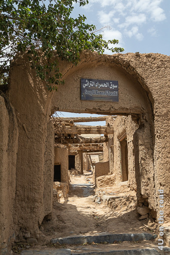 Al Hamra - der alte Souk. Im Bild sieht man den Eingang des den Hügel hinaufgehenden Souks. Ehemals überdacht, ist das Dach an vielen Stellen eingebrochen. Der Weg zwischen den festen Verkaufsständen ist schmal.