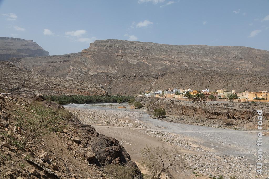 Al Jiraifat - Auf dem Weg zum Jebel Shams. Vor dem Hintergrund hoher Berge ist ein Flussbett tief eingeschnitten. Auf dem rechten Ufer befindet sich ein Ort. Wege führen durch das trockene Flussbett.