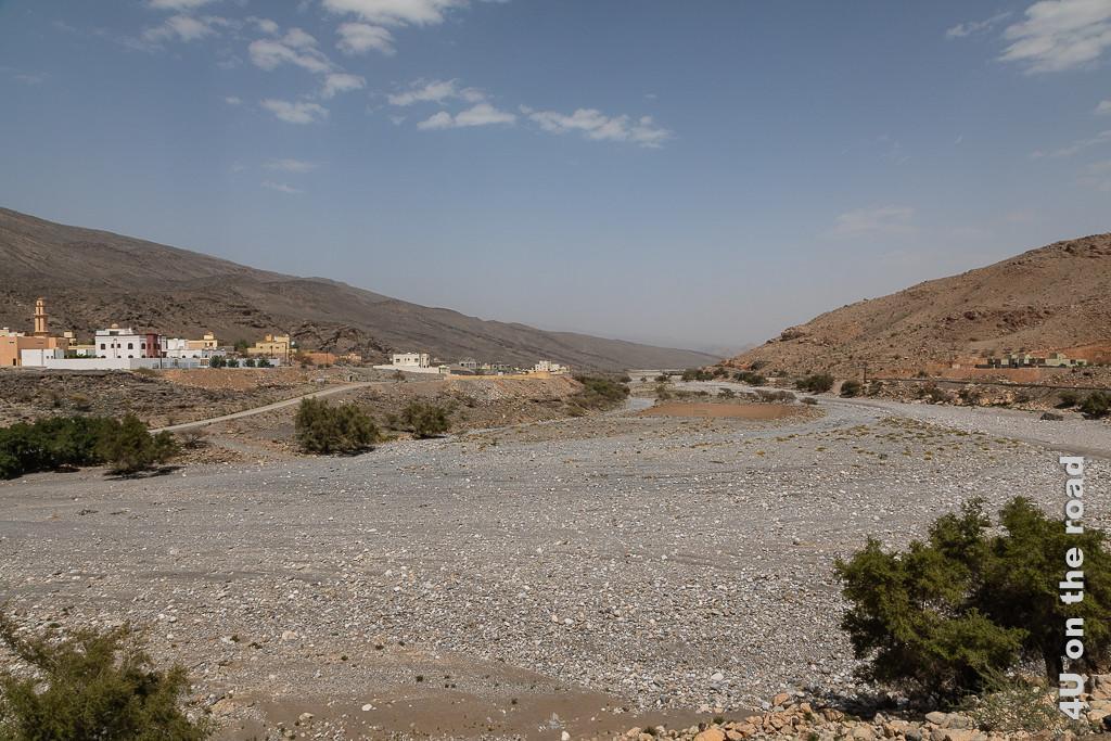 Al Jiraifat - Fussballfeld im trockenen Flussbett. Im Blick zurück sieht man das breite Tal mit dem trockenen Flussbett. Im Flussbett wurden die Steine weggeräumt und so ein sandiges Fussballfeld geschaffen. Links befindet sich der Ort, rechts neben dem Fluss verläuft die Strasse.